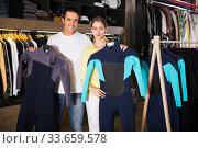 Купить «Couple searching wetsuits for surf», фото № 33659578, снято 7 октября 2019 г. (c) Яков Филимонов / Фотобанк Лори