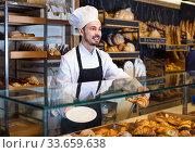 Купить «Man baker showing warm tasty croissant», фото № 33659638, снято 26 января 2017 г. (c) Яков Филимонов / Фотобанк Лори