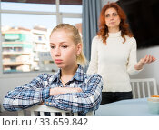 Upset mature woman talking with sad daughter at home. Стоковое фото, фотограф Яков Филимонов / Фотобанк Лори