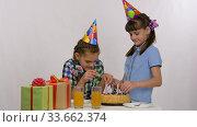 Две девочки вставляют свечки в праздничный торт. Стоковое видео, видеограф Иванов Алексей / Фотобанк Лори