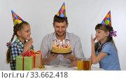 Дети целуют папу который сидит за столом с праздничным тортом. Стоковое видео, видеограф Иванов Алексей / Фотобанк Лори