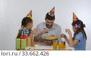 Папа с дочерьми делят праздничный торт, вытаскивают свечи выкидывают их назад. Стоковое видео, видеограф Иванов Алексей / Фотобанк Лори