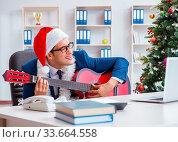 Купить «The businessman celebrating christmas holiday in the office», фото № 33664558, снято 10 июля 2020 г. (c) easy Fotostock / Фотобанк Лори