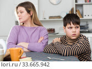 Upset mother and unhappy son sitting after quarrel indoors. Стоковое фото, фотограф Яков Филимонов / Фотобанк Лори