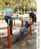 Купить «Family exercising on parallel bars outdoors», фото № 33666062, снято 11 ноября 2018 г. (c) Яков Филимонов / Фотобанк Лори