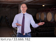 Winemaker inviting to wine cellar. Стоковое фото, фотограф Яков Филимонов / Фотобанк Лори