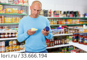 Portrait of young man making purchases in the grocery store. Стоковое фото, фотограф Яков Филимонов / Фотобанк Лори