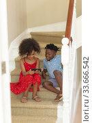 Купить «Mixed race girl and her younger brother using phone at home», фото № 33666542, снято 28 ноября 2019 г. (c) Wavebreak Media / Фотобанк Лори