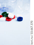 Купить «Colorful plastic caps against bottles. Plastic wrapping rubbish on blue background. Concept of environmental pollution», фото № 33667370, снято 30 апреля 2020 г. (c) Papoyan Irina / Фотобанк Лори