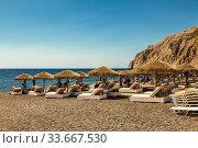 Beach with grey volcanic sand at Kamari, Santorini island, Greece (2017 год). Редакционное фото, фотограф Наталья Волкова / Фотобанк Лори