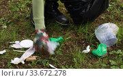 Купить «Volunteer woman in gloves collects trash in the black trash bag. Trash free planet concept. Nature cleaning, volunteer ecology green concept. Environment plastic pollution.», видеоролик № 33672278, снято 1 мая 2020 г. (c) Алексей Кузнецов / Фотобанк Лори