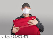 Купить «Frightened tourist man in a medical mask presses with red suitcase, the concept cant leave the country, flights canceled», фото № 33672478, снято 18 марта 2020 г. (c) katalinks / Фотобанк Лори