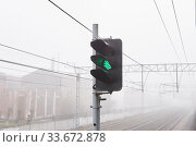 Купить «Railroad rails lurking in fog, in the foreground the LED railway signal is green», фото № 33672878, снято 27 апреля 2020 г. (c) Евгений Харитонов / Фотобанк Лори