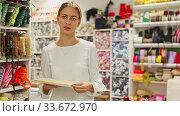 Купить «Smiling young saleswoman offering colorful ribbons and braid for sewing in haberdasher shop», видеоролик № 33672970, снято 15 июля 2020 г. (c) Яков Филимонов / Фотобанк Лори