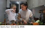 Купить «Happy mother and little daughter preparing soup together at home, cut vegetable», видеоролик № 33672994, снято 20 января 2020 г. (c) Яков Филимонов / Фотобанк Лори