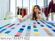 Купить «Wide angle view a young adult fashion designer drawing and sketching her work at her atelier studio with colour palette as sole owner. Using for entrepreneur startup concept.», фото № 33677022, снято 11 июля 2020 г. (c) easy Fotostock / Фотобанк Лори
