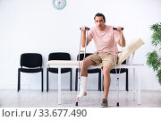 Купить «Young injured man waiting for his turn in hospital hall», фото № 33677490, снято 3 мая 2019 г. (c) Elnur / Фотобанк Лори