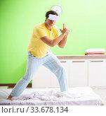 Купить «Young man with virtual glasses in the bedroom», фото № 33678134, снято 22 июня 2018 г. (c) Elnur / Фотобанк Лори