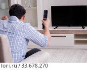 Купить «Young man watching tv at home», фото № 33678270, снято 9 марта 2018 г. (c) Elnur / Фотобанк Лори