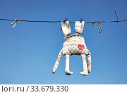 Forgotten old faded toy of bunny hanging on a clothesline on background blue sky. Стоковое фото, фотограф Олег Белов / Фотобанк Лори