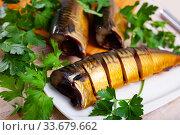 Smoked mackerel cut into pieces with parsley on a table. Стоковое фото, фотограф Яков Филимонов / Фотобанк Лори