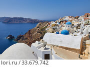 Oia, Santorini, Greece, August 21, 2013: View of the city, sea and volcanic slopes of the island. Редакционное фото, фотограф Олег Белов / Фотобанк Лори