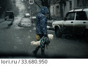 Saratov, Russia - 03/14/2020: Street photo, city life, a woman carrying a dirty dog in her hands as a bag across the road in bad cloudy weather with snow and puddles in an empty city down the street. Стоковое фото, фотограф Светлана Евграфова / Фотобанк Лори