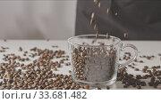 Купить «Roasted coffee beans are pouring in a glass cup and table.», видеоролик № 33681482, снято 31 августа 2018 г. (c) Ярослав Данильченко / Фотобанк Лори
