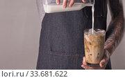 The man with tatoo makes refreshing ice coffee with milk. Стоковое видео, видеограф Ярослав Данильченко / Фотобанк Лори