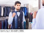 Купить «Customer male is picking up tie for waistcoat in front of the mirror», фото № 33681986, снято 20 июня 2017 г. (c) Яков Филимонов / Фотобанк Лори