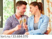Junges verliebtes Paar feiert Verlobung oder Versöhnung mit einem Glas Sekt. Стоковое фото, фотограф Zoonar.com/Robert Kneschke / age Fotostock / Фотобанк Лори