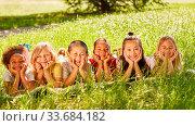 Купить «Glückliche multikulturelle Kinder liegen im Sommer auf einer grünen Wiese als Konzept für Integration und Freundschaft», фото № 33684182, снято 26 мая 2020 г. (c) age Fotostock / Фотобанк Лори