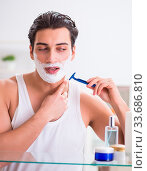 Купить «The young handsome man shaving early in the morning at home», фото № 33686810, снято 3 июля 2020 г. (c) easy Fotostock / Фотобанк Лори