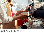 Купить «Close-up shot of a barista brewing coffee by modern coffeemaker machine to making a cup of coffee with other barista working in background. Using for small business entrepreneur owner concept.», фото № 33689154, снято 10 июля 2020 г. (c) easy Fotostock / Фотобанк Лори