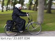 Nun in a bicycle at Beguinage De Wijngaard, Bruges, Belgium. Now a monastery of Benedictine sisters. Редакционное фото, фотограф Sergi Reboredo / age Fotostock / Фотобанк Лори