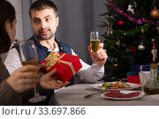 Couple celebrating New Year, woman giving present to man. Стоковое фото, фотограф Яков Филимонов / Фотобанк Лори