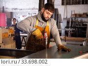 Купить «Confident man mechanic drilling metal sheet in workshop», фото № 33698002, снято 4 августа 2020 г. (c) Яков Филимонов / Фотобанк Лори