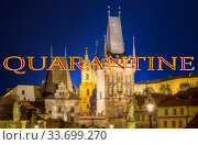 Coronavirus in Prague, Czech Republic. Mala Strana Bridge Tower at Charles Bridge. Quarantine sign on a blurred background. Concept of COVID pandemic and travel in Europe. (2019 год). Стоковое фото, фотограф Владимир Журавлев / Фотобанк Лори