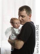 Молодой папа в черной футболке с нежностью держит маленькую дочку. У младенца крылья ангела. Стоковое фото, фотограф Наталья Гармашева / Фотобанк Лори