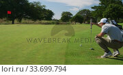 Caucasian male golfer kneeling on a golf course on a sunny day. Стоковое видео, агентство Wavebreak Media / Фотобанк Лори