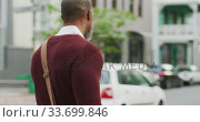 Купить «African American Man walking in the street with his bike», видеоролик № 33699846, снято 11 марта 2020 г. (c) Wavebreak Media / Фотобанк Лори