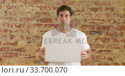 Купить «Caucasian man holding a white rectangle on a brick wall», видеоролик № 33700070, снято 23 июля 2019 г. (c) Wavebreak Media / Фотобанк Лори