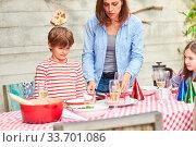 Mutter und Kinder zusammen am Esstisch im Garten auf einem Sommerfest. Стоковое фото, фотограф Zoonar.com/Robert Kneschke / age Fotostock / Фотобанк Лори