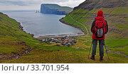 Eine Wandererin schaut auf den kleinen Ort Tjørnuvík und den Atlantik, Streymoy, Faeroeer, Føroyar, Daenemark, Europa. Стоковое фото, фотограф Zoonar.com/Stefan Ziese / age Fotostock / Фотобанк Лори
