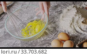Купить «Woman's hands start to whip fresh natural eggs in a glass bowl by whisk for preparation homemade cake on a table with flour an raw eggs. Slow motion, Full HD video, 240fps, 1080p.», видеоролик № 33703682, снято 31 августа 2018 г. (c) Ярослав Данильченко / Фотобанк Лори