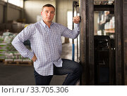 Купить «Seller is standing near loader in the building store», фото № 33705306, снято 9 октября 2019 г. (c) Яков Филимонов / Фотобанк Лори