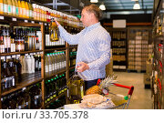 Купить «Male customer choosing olive oil in average food shop», фото № 33705378, снято 9 октября 2019 г. (c) Яков Филимонов / Фотобанк Лори