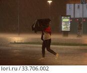 Москва, девушка под зонтом в сильный ливень в дни коронавирусной пандемии COVID-19 (2020 год). Редакционное фото, фотограф Дмитрий Неумоин / Фотобанк Лори