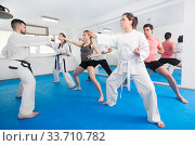 Young adult trainees practicing in karate class. Стоковое фото, фотограф Яков Филимонов / Фотобанк Лори