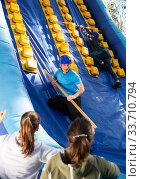 Купить «Friends climbing on inflatable slide in amusement park», фото № 33710794, снято 26 мая 2020 г. (c) Яков Филимонов / Фотобанк Лори
